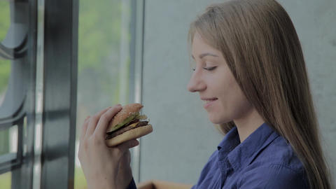 Beautiful girl holding a burger in her hands. Fast food restaurant Footage