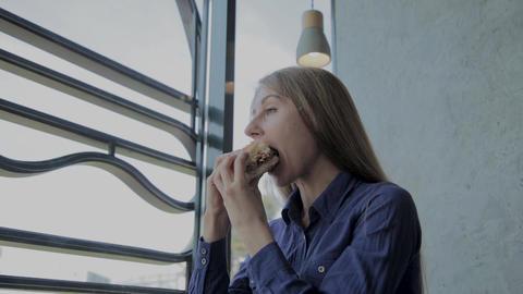 Beautiful girl eats a burger. Fast food restaurant Footage