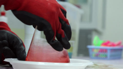 A lab technician mixes a pink liquid in the flask Footage