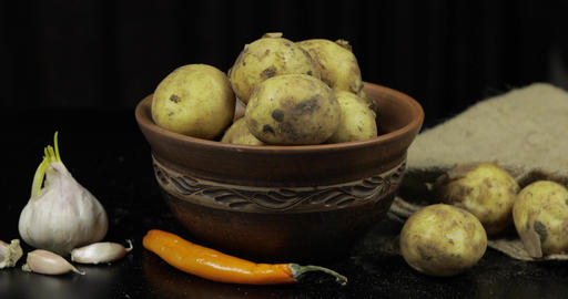 Dirty raw potatoes on a plate on table with garlic and pepper Footage