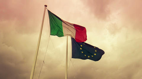 waving fabric texture of the flag of italy and union europe on sunset sky with clouds, concept of Footage