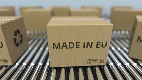 Boxes with MADE IN EU text on roller conveyor. European Union goods related Footage