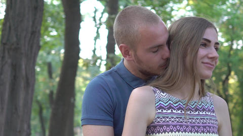 Slow Motion Young Couple Embracing. The Guy Embraces And Kisses The Girl Live Action