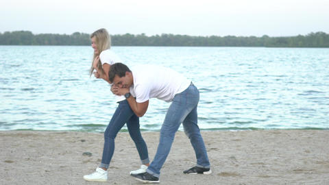 Happy Young Couple Having Fun Together On The Beach, Slowmotion Live Action