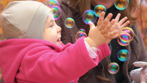 Young Family Playing With Baby In Autumn Park. Playing With Soap Bubbles Live Action