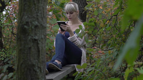 Real Time Young Woman With Tablet Computer In Beautiful Autumn Park Footage