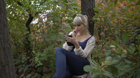 4K Teenage Girl Standing In The Park And Texting On Cellphone, Steadycam Shot Footage