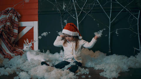4K The Girl In The Cap Of Santa Claus Throws The Snow Up. Artificial Snow Footage