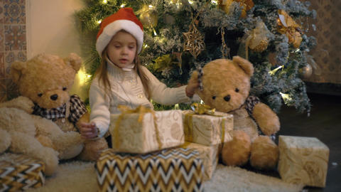 4K White Happy Kid Looks At Holiday Presents Siting Under Christmas Tree Footage