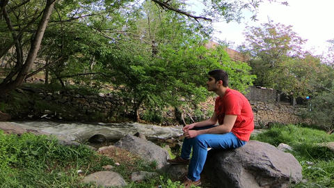Man sitting next to the river ビデオ