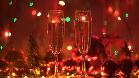 4K Two Glasses With Sparkling Champagne Over Holiday Blinking Background Footage