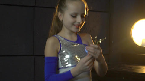 Young Positive Smiling Girl Holds Gold Winner Cup In The Hands Live Action