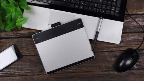 Graphic designer workplace. Graphic tablet and stylus, laptop and phone. Camera Live-Action