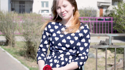 Cute girl smiles and walks with a red rose in her hands video footage Footage