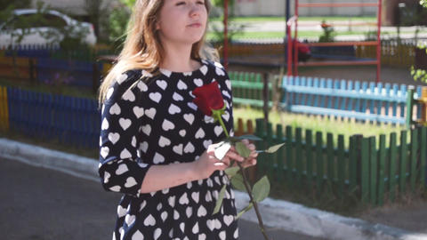 Girl walking with a red rose in the city Footage