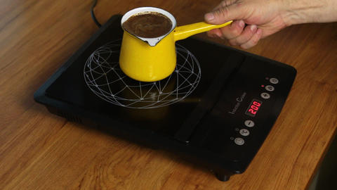 Person makes coffee by adjusting the power of the induction stove Footage