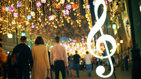 Unrecognizable people walking along beautiful illuminated pedestrian street in Footage