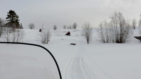 tourists in warm equipment drive snowmobile and cross hills Footage