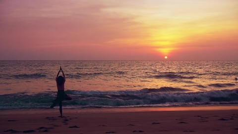 Young beautiful woman doing yoga on beach at sunset - tree pose slow motion - gr Footage