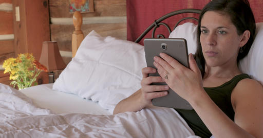 Attractive young woman using a tablet in a vertical position as if reading a digital book in her Footage