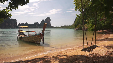 Long tail boat near sandy beach with swing Live Action