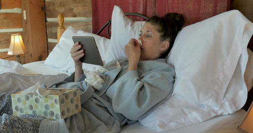 Woman with a cough and runny nose video chatting with a tablet in bed talking to a medical Footage