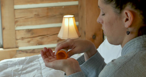 Young woman emptying pills from a prescription medicine bottle into her hand in her bed before going Live Action