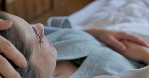 Hand compassionately caresses a woman's head lying in bed wearing a bathrobe GIF