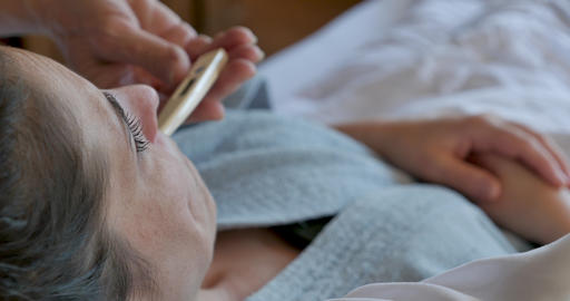 Close up of a hand removing a digital thermometer from a woman's mouth while she lies in bed in a GIF