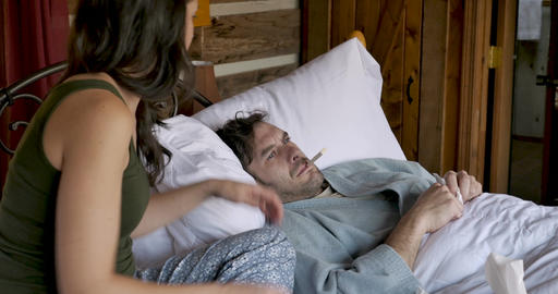 Woman looking at a digital thermometer after taking her husbands temperature while he is lying in GIF