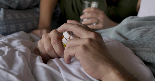 Close up of a man opening up a childproof cap of a prescription medicine bottle and putting the lid GIF