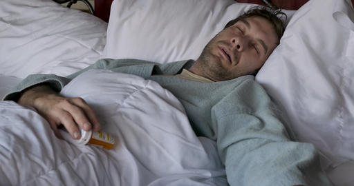 Man lying unconscious in bed dropping a pill bottle that he was holding in his hand Footage