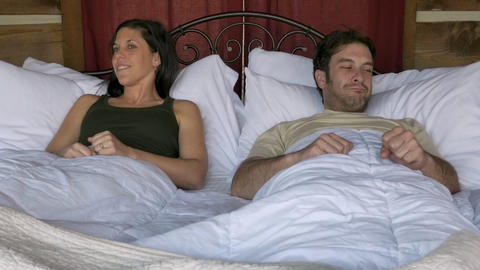 Happy couple lifting their heads at the same time in the morning, smiling, and dancing in bed Footage