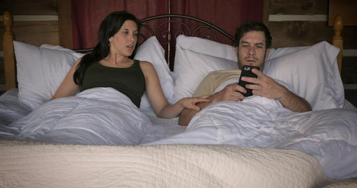 Man and woman hear a noise, wake up, check their smart home security system app on their mobile GIF