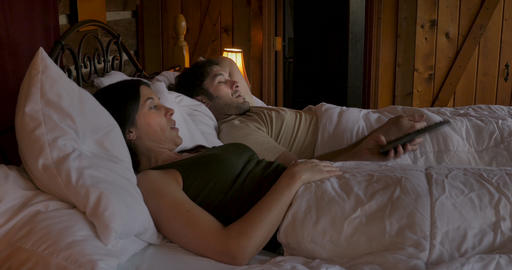 Attractive woman takes a TV remote from a man while watching television in bed - dolly shot GIF