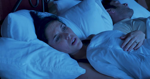 Young mother or wife, or girlfriend lying awake in bed at night unable to sleep worried and Footage