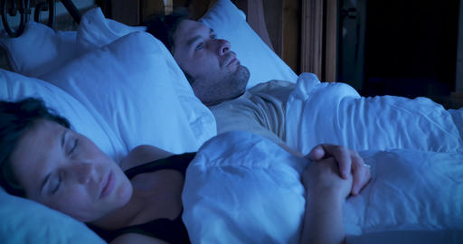 Angry, irritated man lying in bed frowning, and crossing his arms next to a sleeping woman at night Footage
