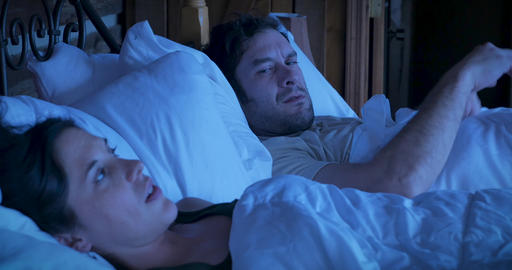 Man and woman with relationship troubles angry at each other while lying in bed at night Footage