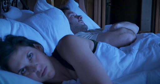 Rack focus from man to woman of a couple angry having relationship problems lying in bed at night, Live Action