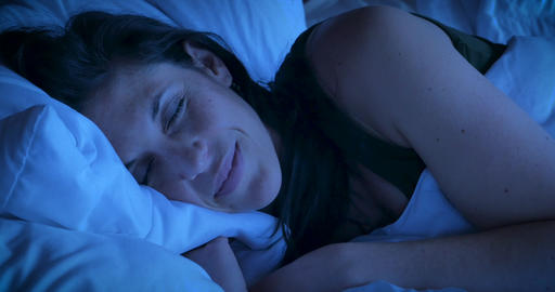 Close up of an attractive woman smiling while sleeping at night having good dreams or a comfortable GIF