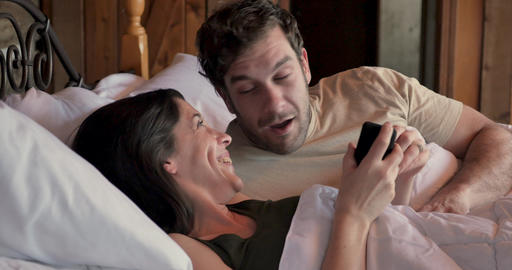 Beautiful young woman surprising a man by giving him a ring in bed as if she is proposing to him Footage