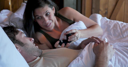 Young pretty woman proposing to a handsome man giving him an engagement ring in bed Footage