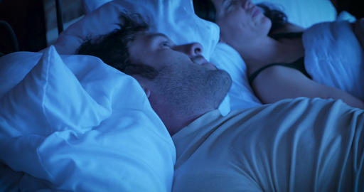 Antsy uncomfortable man moving around a lot in bed trying to fall asleep showing his frustration at GIF