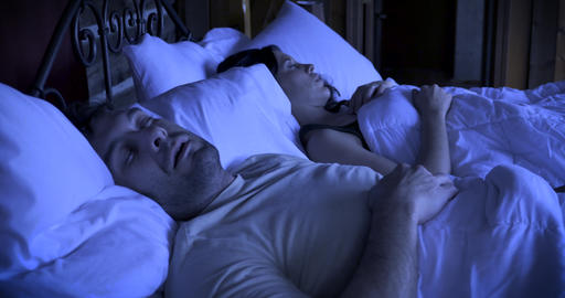 Man reluctantly wakes up in the dark from an alarm or phone call on his mobile device while lying in GIF