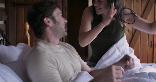 Attractive man and young woman happy dancing with each other celebrating life in bed in the morning Footage