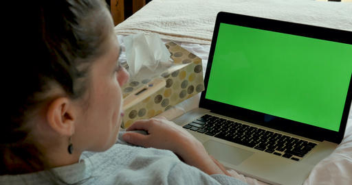 Sick woman lying in bed taking her temperature with a digital thermometer with a green screen laptop Footage