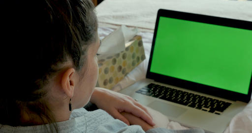 Sick young woman talking to a green screen computer while blowing her nose and lying in bed as if GIF