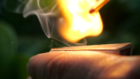 Slow motion of lighting a match. Close up of hands lighting a match. The wooden Live Action