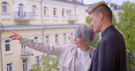 Millenial couple standing on balcony and girl points finger showing green and Footage
