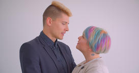 Millenial caucasian couple hugging tenderly on white background watching at each Footage
